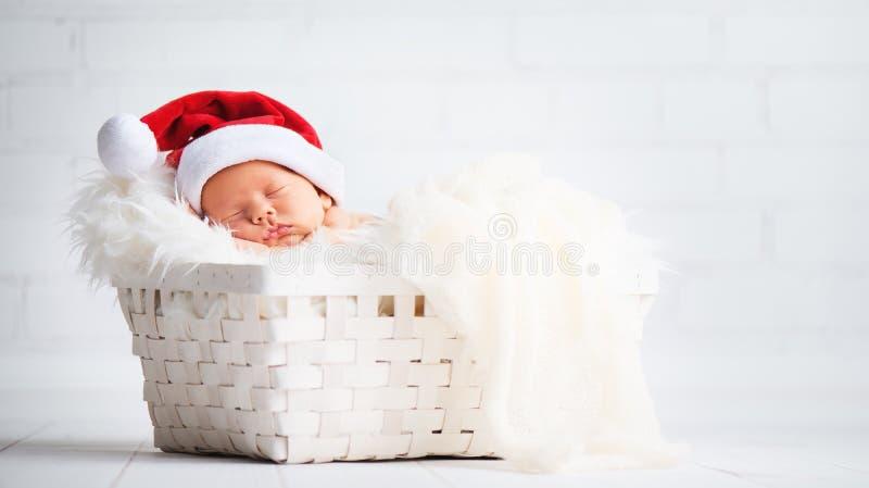 Bebé recién nacido del durmiente en el casquillo de Papá Noel de la Navidad foto de archivo libre de regalías