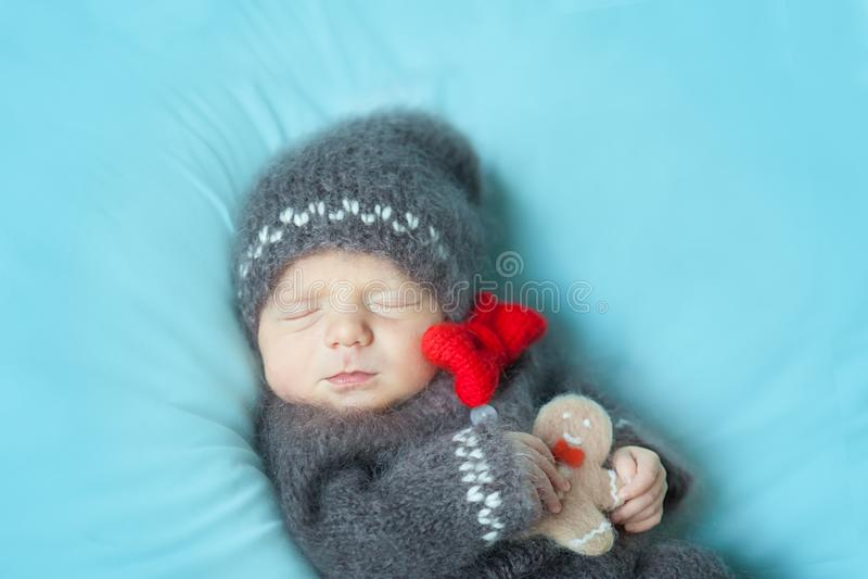 Bebé recién nacido durmiente en un traje hecho a ganchillo del hombre de pan de jengibre imagen de archivo