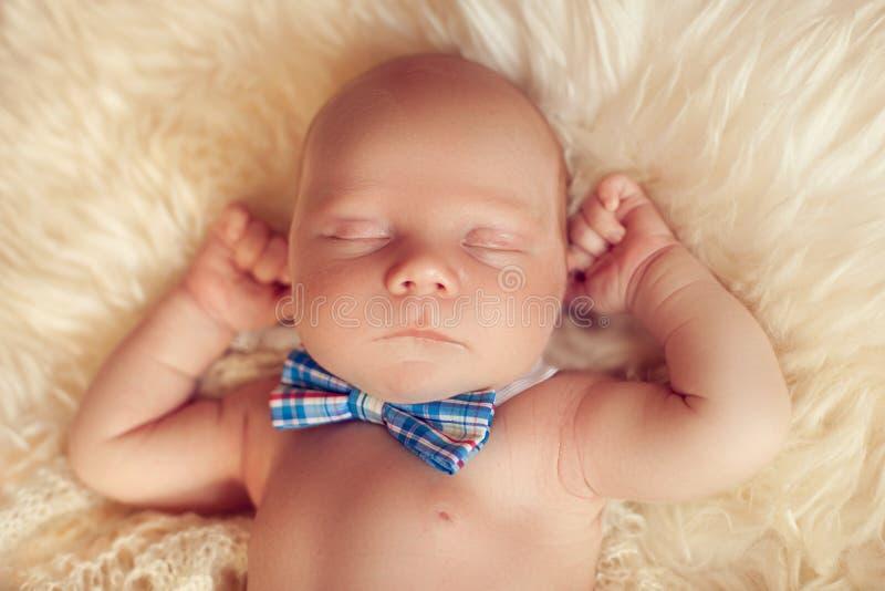 Bebé recién nacido durmiente que miente con la corbata de lazo en una piel blanca en h foto de archivo libre de regalías