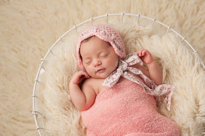 Bebé recién nacido en la cesta que lleva un capo rosado fotos de archivo libres de regalías