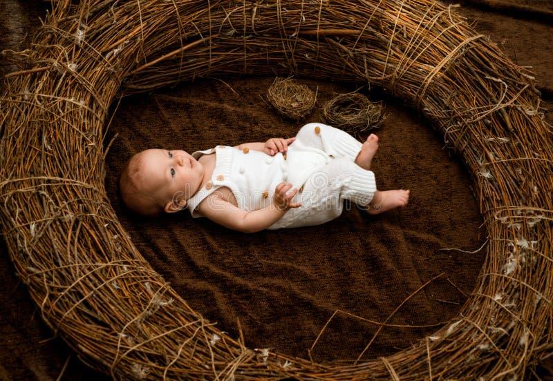Bebé recién nacido en pesebre de mimbre Bebé o muchacho recién nacido La atención sanitaria primaria incluye al médico de cabecer imagen de archivo libre de regalías