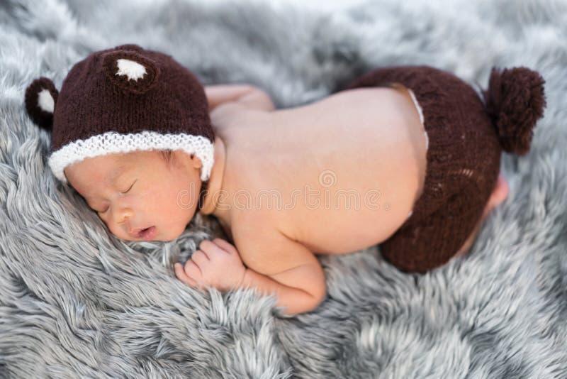 Bebé recién nacido en sombrero del oso que duerme en cama de la piel fotos de archivo libres de regalías