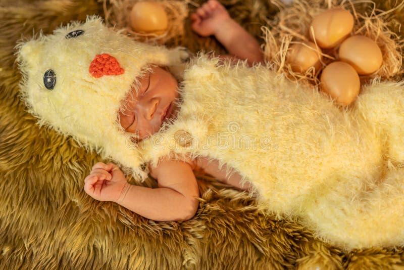 Bebé recién nacido en traje del pollo que duerme en cama de la piel foto de archivo