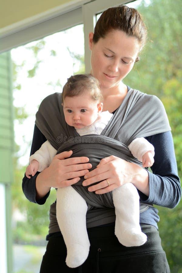Bebé recién nacido en un abrigo de la honda del bebé fotos de archivo libres de regalías