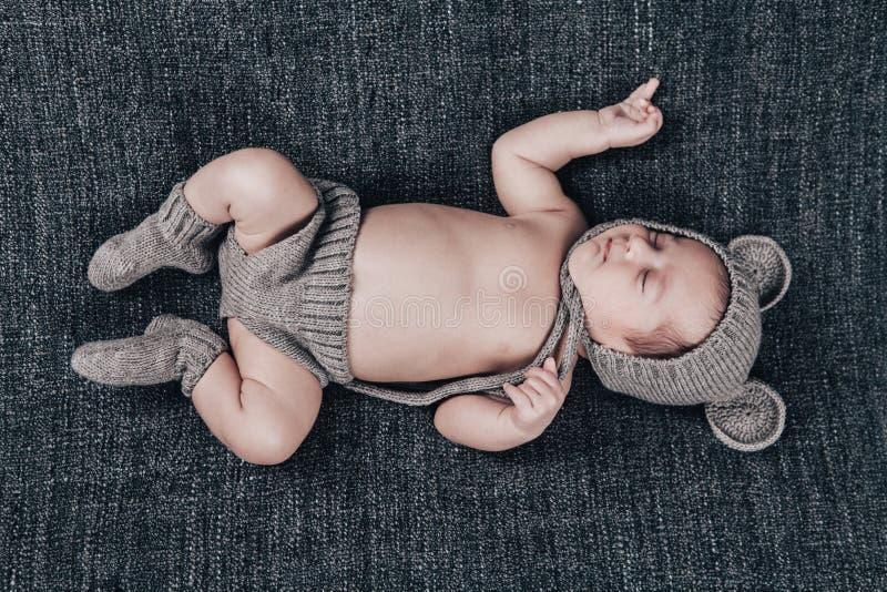 Bebé recién nacido en un traje hecho punto dormido en una tela escocesa gris fotos de archivo libres de regalías