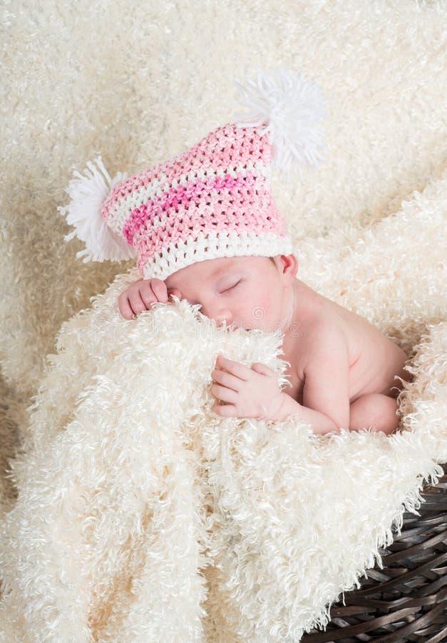 Bebé recién nacido hermoso que lleva un sombrero rosado con los poms blancos del pom fotografía de archivo libre de regalías