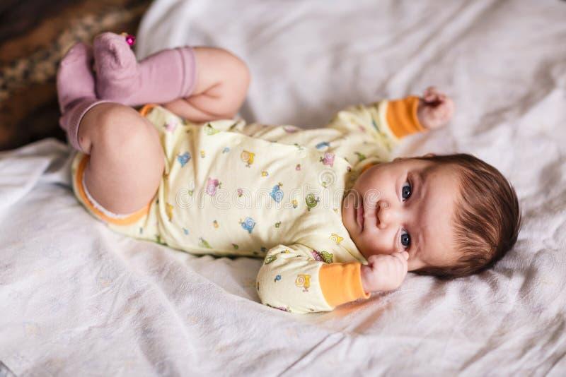 Bebé recién nacido lindo que miente en cama fotografía de archivo