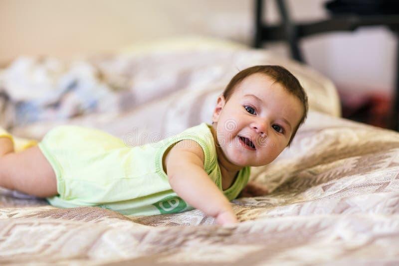 Bebé recién nacido lindo que miente en cama foto de archivo libre de regalías