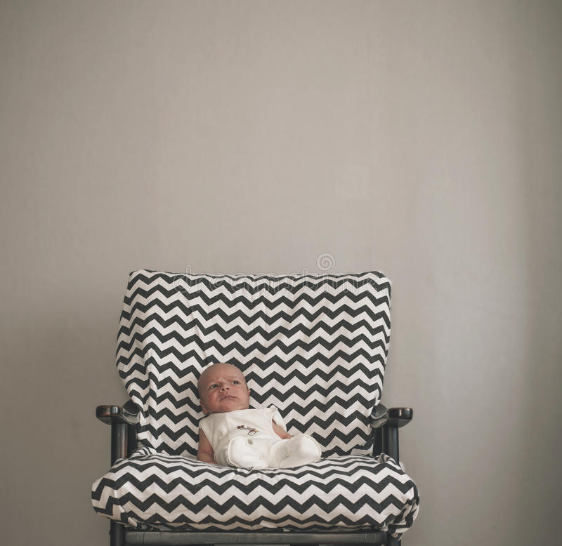 Bebé recién nacido lindo que se sienta en la silla grande imagen de archivo