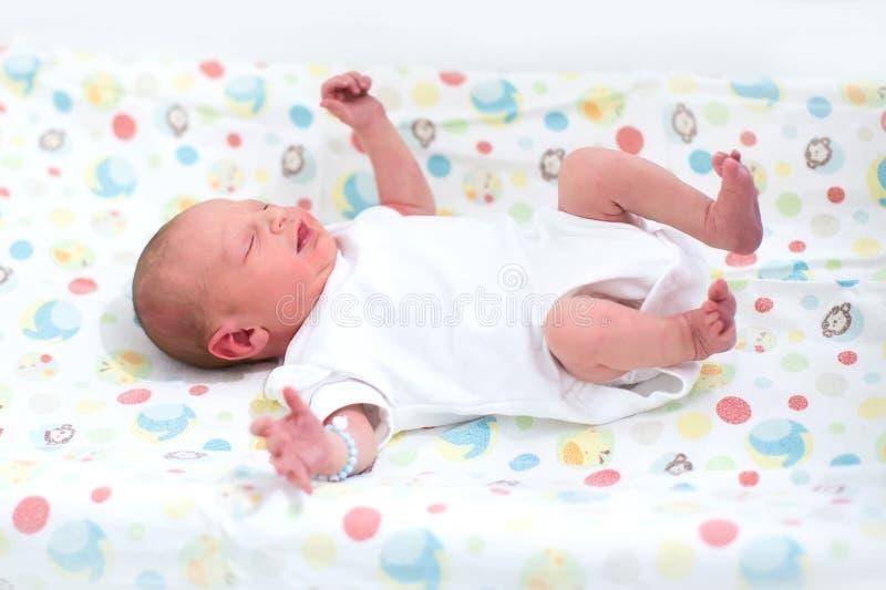 Bebé recién nacido minúsculo en una tabla cambiante foto de archivo