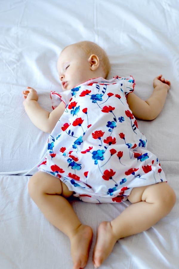 Bebé recién nacido pacífico que miente en una cama fotos de archivo