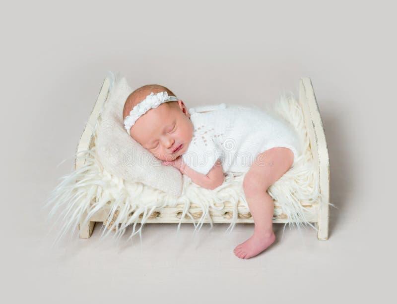 Bebé recién nacido precioso que duerme en el pesebre con la pierna en el piso foto de archivo