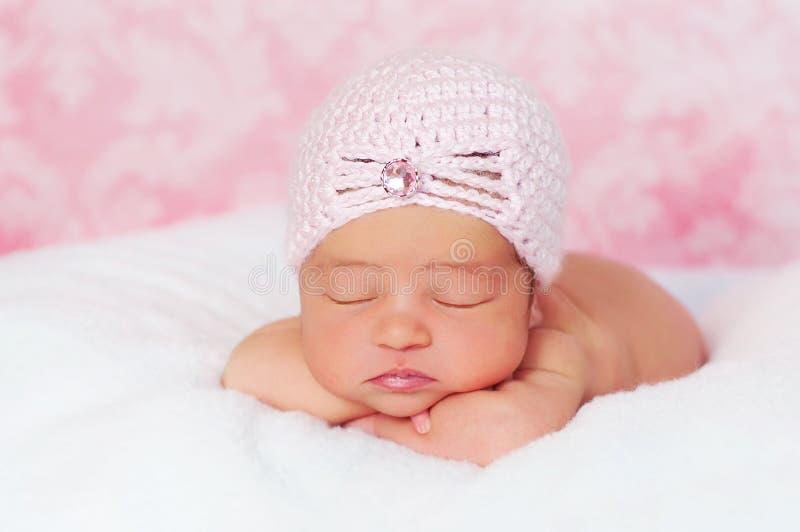 Bebé recién nacido que desgasta un sombrero rosado del estilo de la aleta fotos de archivo libres de regalías