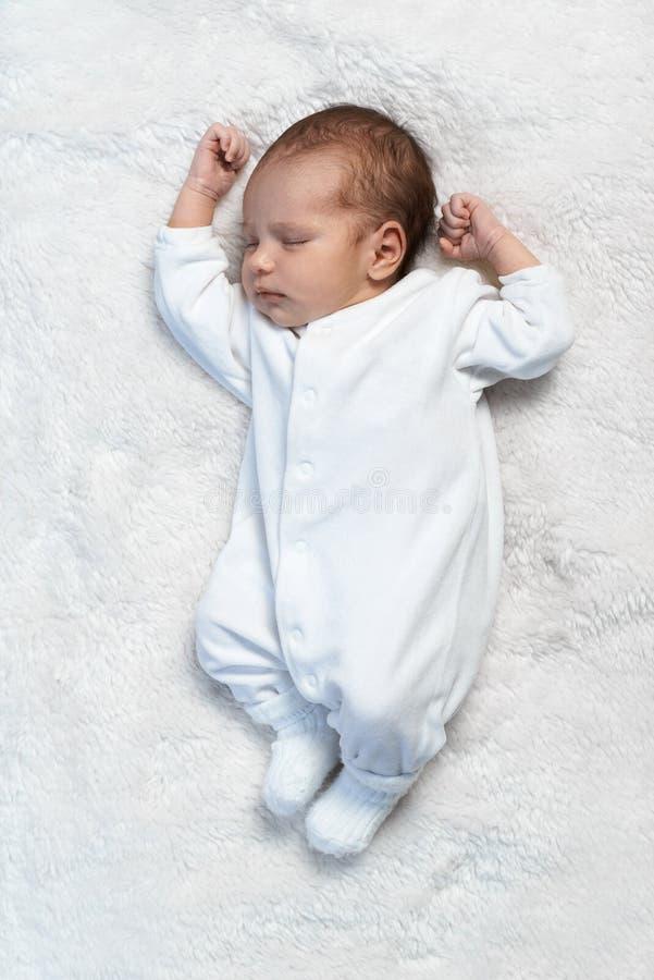 Bebé recién nacido que duerme en la piel blanca en luz del sol imagenes de archivo