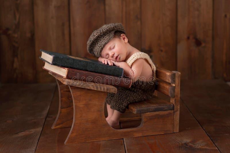 Bebé recién nacido que duerme en su escritorio de la escuela imagenes de archivo