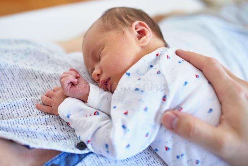 Bebé recién nacido que duerme en su pecho del ` s del padre imagen de archivo