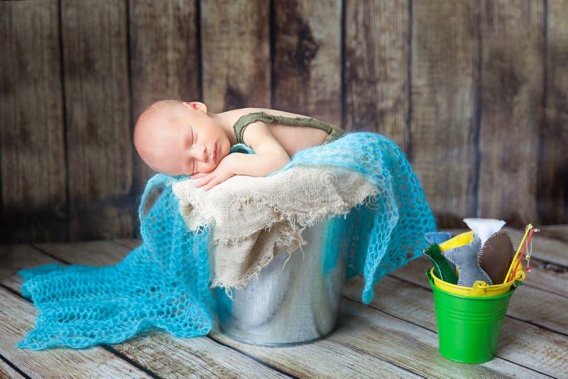 Bebé recién nacido que duerme en un cubo del metal plateado imagenes de archivo
