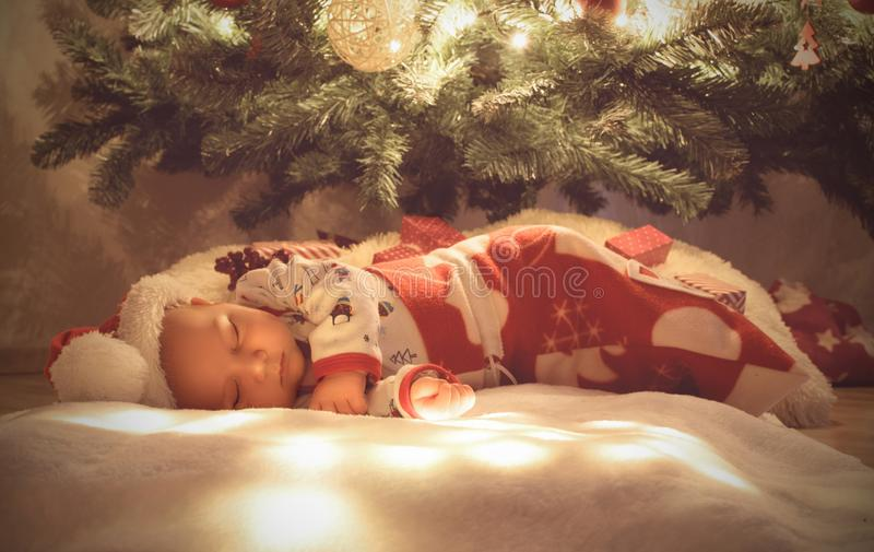 Bebé recién nacido que duerme y que sueña debajo del árbol de navidad envuelto en el bolso de la Navidad el dormir fotos de archivo