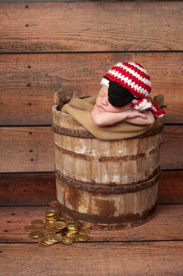 Bebé recién nacido que lleva un remiendo del sombrero y del ojo del pirata imagenes de archivo