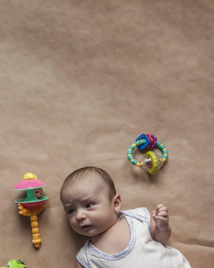 Bebé recién nacido que miente con los juguetes Primer del bebé recién nacido lindo adorable de dos meses y juguetes El jugar prec fotografía de archivo