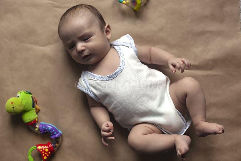 Bebé recién nacido que miente con los juguetes Primer del bebé recién nacido lindo adorable de dos meses y juguetes El jugar prec imagen de archivo libre de regalías