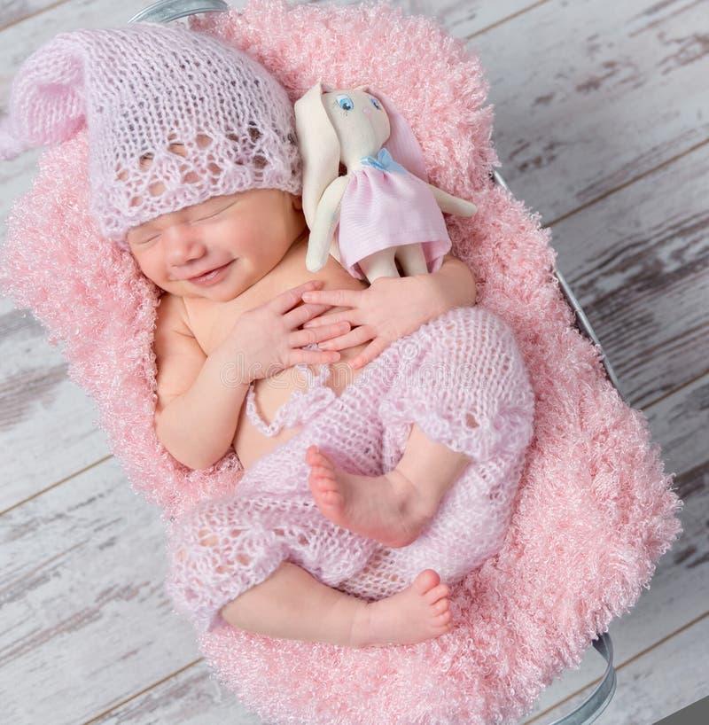 Bebé recién nacido sonriente con una liebre del juguete fotos de archivo libres de regalías