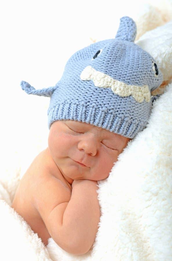 Bebé recién nacido sonriente en sombrero del tiburón fotos de archivo