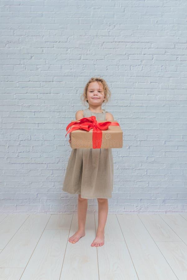 Bebé, regalo de cumpleaños de la muchacha, día de fiesta, la Navidad, pared de ladrillo blanca b fotos de archivo