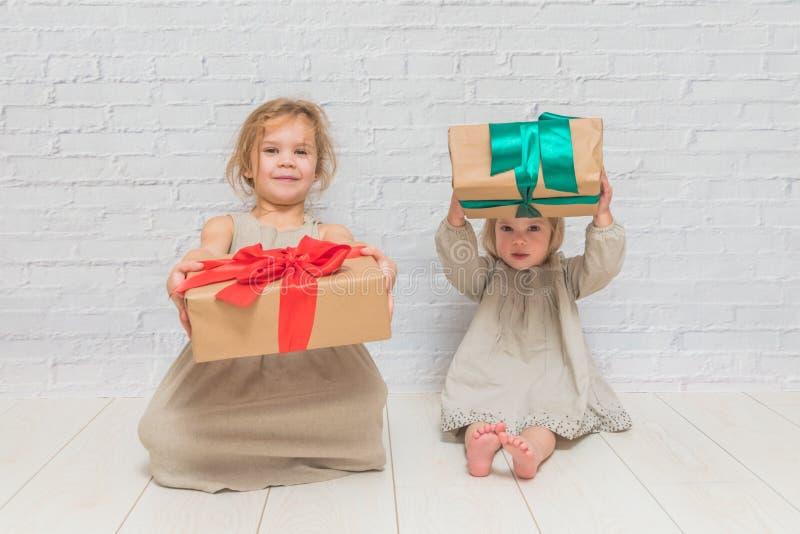 Bebé, regalo de cumpleaños de la muchacha, día de fiesta, la Navidad, pared de ladrillo blanca b fotografía de archivo libre de regalías
