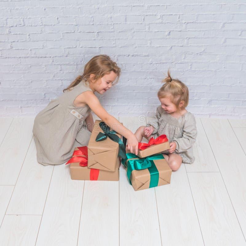 Bebé, regalo de cumpleaños de la muchacha, día de fiesta, la Navidad, pared de ladrillo blanca b imagenes de archivo