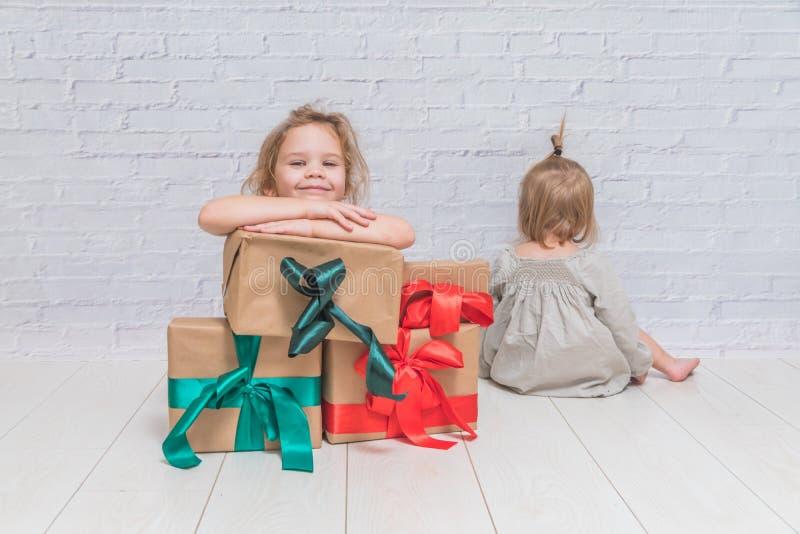 Bebé, regalo de cumpleaños de la muchacha, día de fiesta, la Navidad, pared de ladrillo blanca b fotografía de archivo