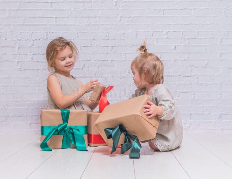 Bebé, regalo de cumpleaños de la muchacha, día de fiesta, la Navidad, pared de ladrillo blanca b imágenes de archivo libres de regalías