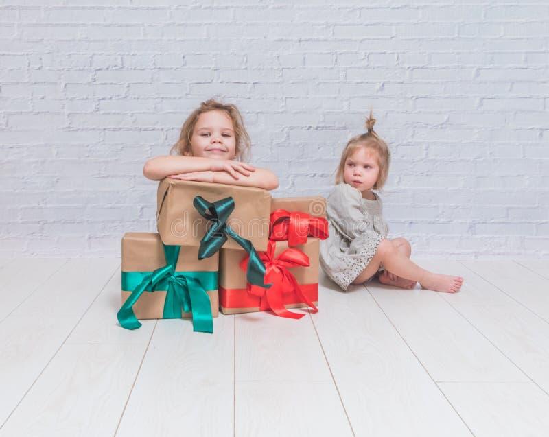 Bebé, regalo de cumpleaños de la muchacha, día de fiesta, la Navidad, pared de ladrillo blanca b foto de archivo libre de regalías