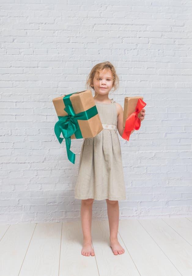 Bebé, regalo de cumpleaños de la muchacha, día de fiesta, la Navidad, pared de ladrillo blanca b foto de archivo