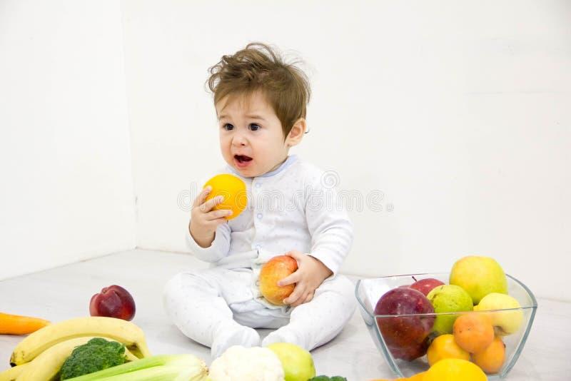 Bebé rodeado con las frutas y verduras, nutrición sana del niño imagen de archivo
