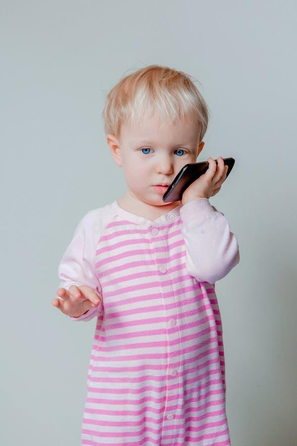 Bebé rubio caucásico con los ojos azules que habla sobre el teléfono celular móvil imágenes de archivo libres de regalías