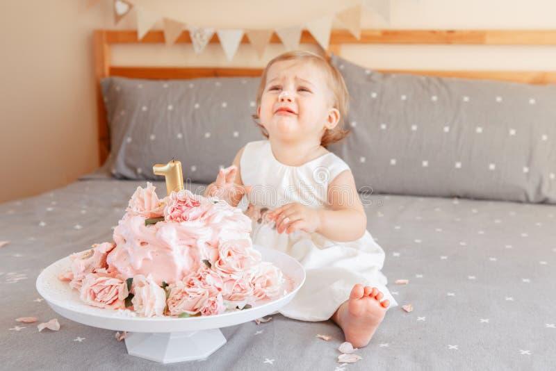 bebé rubio caucásico gritador trastornado en el vestido blanco que celebra su primer cumpleaños foto de archivo