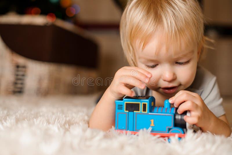 Bebé rubio lindo que juega en la alfombra fotografía de archivo