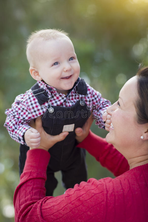 Bebé rubio que juega con su mamá al aire libre fotografía de archivo