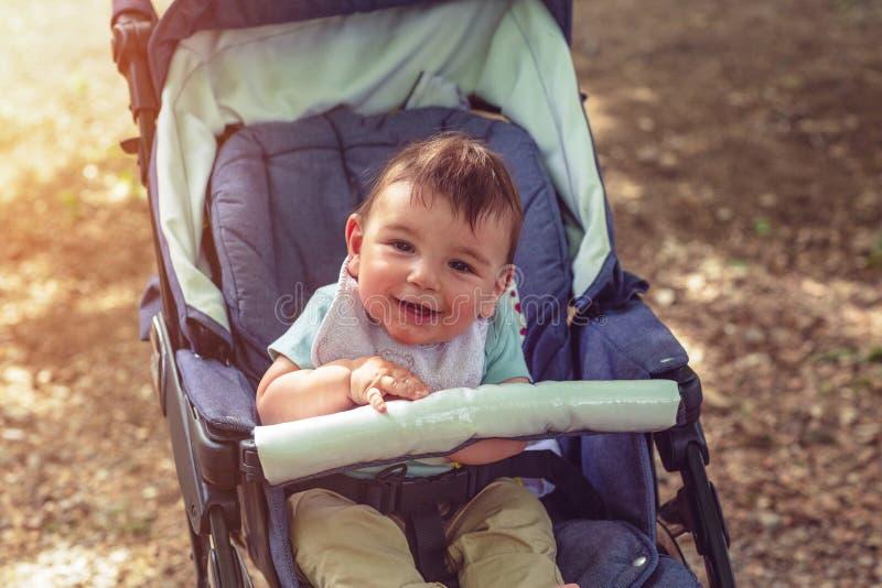 Bebé sonriente adorable que se sienta en un cochecito para un paseo foto de archivo libre de regalías