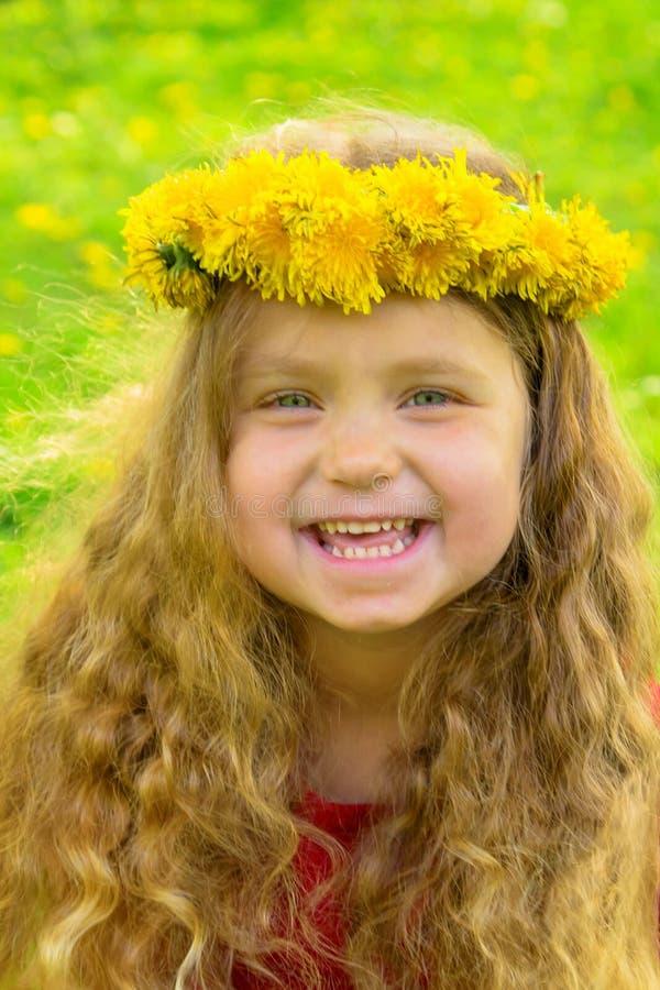 Bebé sonriente con la corona que lleva larga del pelo rubio del dandelio imagenes de archivo