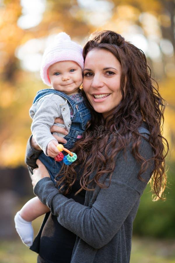 Bebé sonriente de la tenencia de la mamá fotografía de archivo libre de regalías