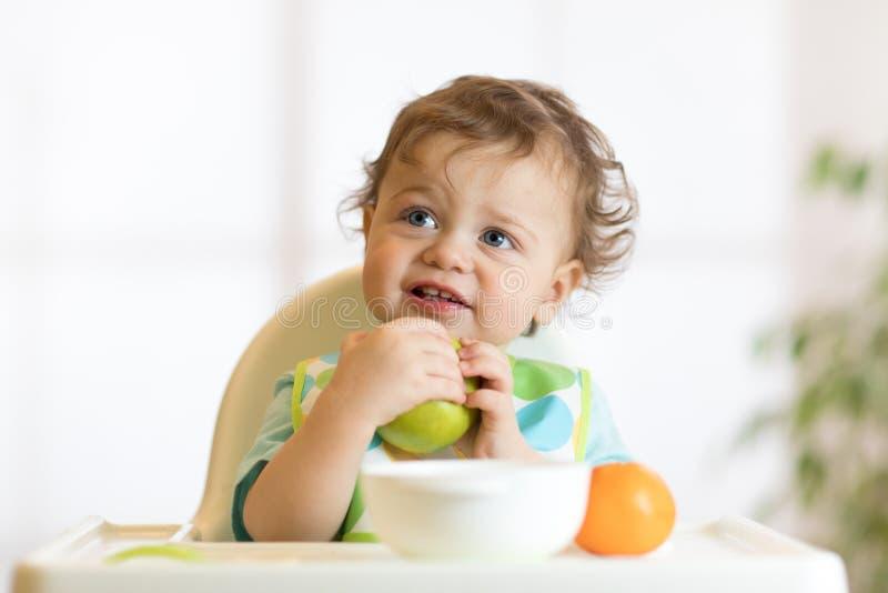 Bebé sonriente del niño del niño que se sienta en highchair y que come el retrato verde grande de la fruta de la manzana dentro imagenes de archivo