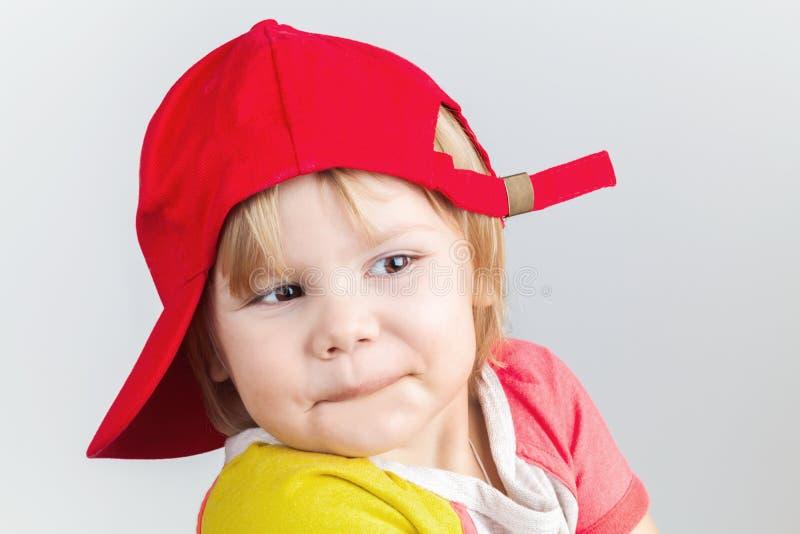 Bebé sonriente divertido en gorra de béisbol roja fotografía de archivo