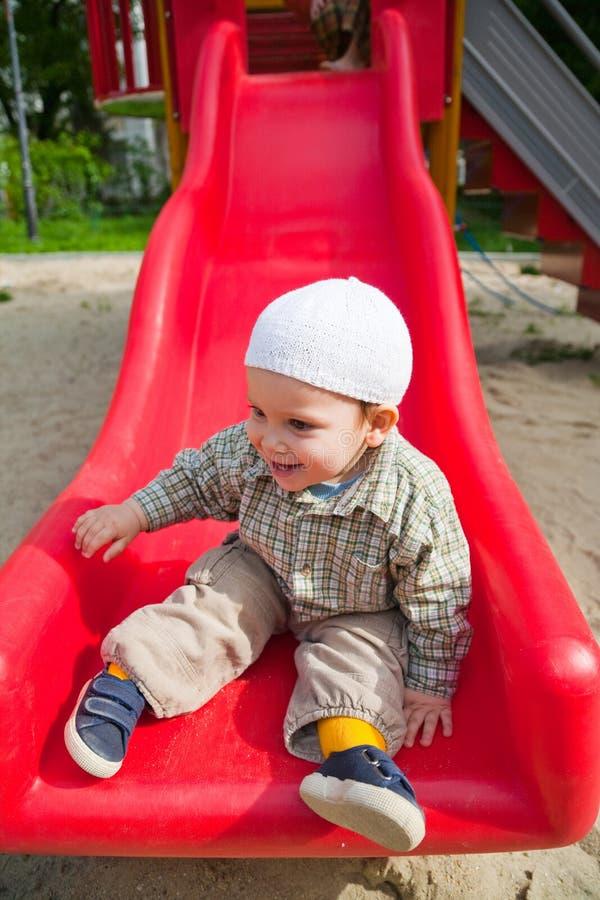 Bebé sonriente en diapositiva imágenes de archivo libres de regalías