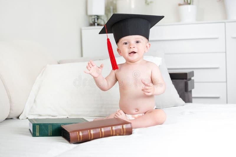 Bebé sonriente en el sombrero negro de la graduación que mira in camera imagen de archivo libre de regalías