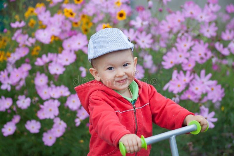 Bebé sonriente feliz que juega en el jardín foto de archivo libre de regalías