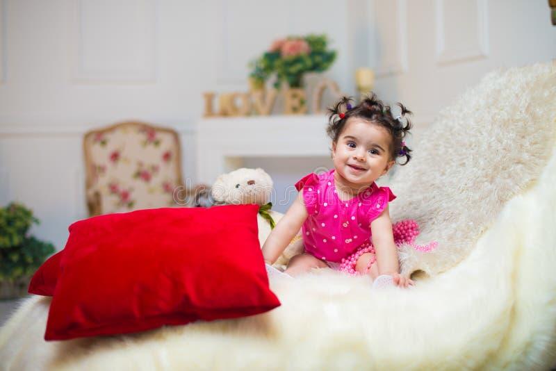 Bebé sonriente feliz que se sienta en el sofá con el juguete del oso imágenes de archivo libres de regalías