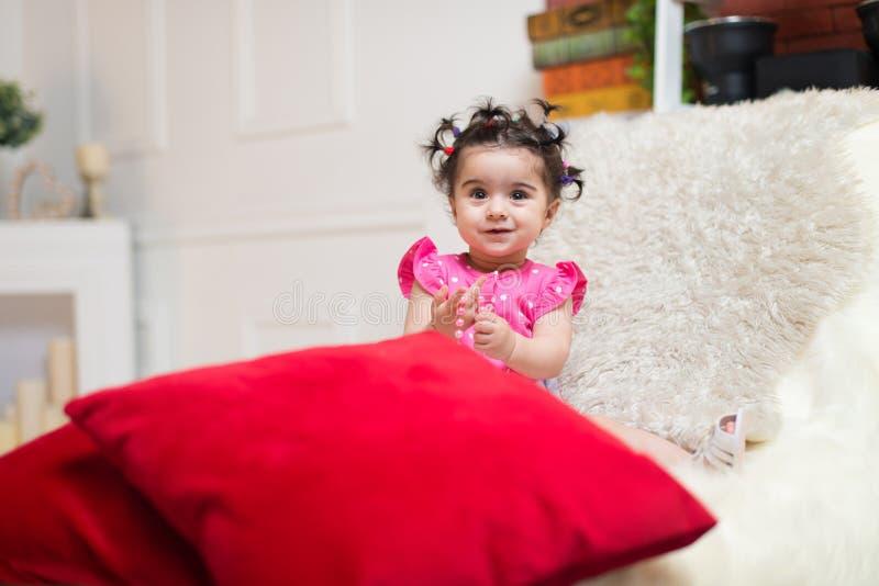 Bebé sonriente feliz que se sienta en el sofá con el juguete del oso imagenes de archivo