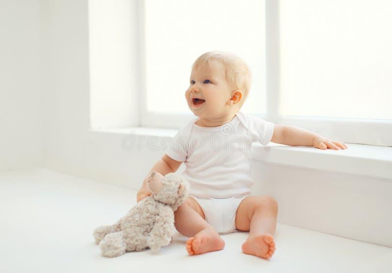 Bebé sonriente lindo con el juguete del oso de peluche que se sienta en casa fotografía de archivo